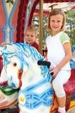 Chłopiec i dziewczyny przejażdżka na carousel Obrazy Stock