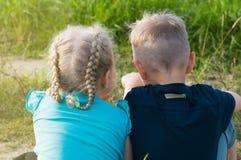 Chłopiec i dziewczyny przyjaciół brata siostrzany obsiadanie na ziemi Obraz Stock
