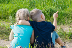Chłopiec i dziewczyny przyjaciół brata siostrzany obsiadanie na ziemi Obrazy Stock