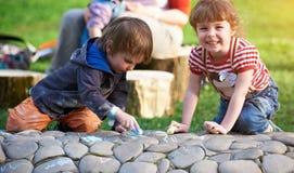 Chłopiec i dziewczyny rysunek z chodniczkiem pisze kredą w parku fotografia royalty free