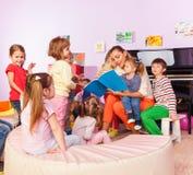 Chłopiec i dziewczyny słuchają nauczyciel czytająca książka zdjęcia royalty free