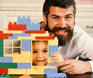 Chłopiec i mężczyzna na defocused tle Ojciec i syn z uśmiechać się twarz chwyt bawimy się cegły budowę obrazy royalty free