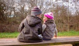 Chłopiec i mała dziewczynka opowiada siedzieć na ławce zdjęcie stock