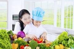 Chłopiec i matki tnący warzywa Obraz Stock