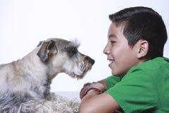 Chłopiec i pies gapimy się przy each inny Obrazy Royalty Free