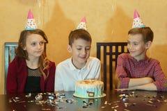 Chłopiec i przyjaciele patrzeje urodzinowego tort urodzinowy tort na wakacyjnym stole przy children& x27; s przyjęcie Zdjęcie Royalty Free