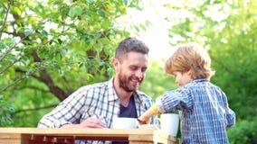 Chłopiec i przystojny ojciec ma śniadanie w ogródzie rodzicielstwo Jedzenie i nap?j dla rodziny Szczęśliwy ojciec z zbiory
