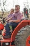 Chłopiec i tata obsiadanie na ciągniku Zdjęcie Royalty Free