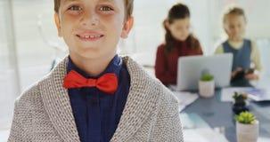 Chłopiec jako dyrektor wykonawczy ono uśmiecha się podczas gdy stojący w biurze 4k zbiory wideo