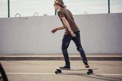 Chłopiec jeździecki longboard na boardwalk, ciepły lato czas obraz royalty free
