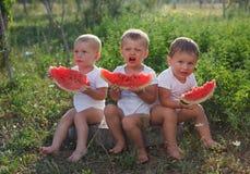 Chłopiec je arbuza outdoors obraz stock