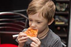 Chłopiec je bardzo smakowitą pizzę z wielką przyjemnością obrazy stock