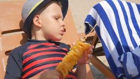 Chłopiec je domowej roboty frytki na kiju na plaży morze, Kłaść na deckchair zbiory wideo