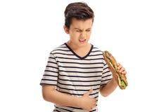 Chłopiec je kanapkę i doświadcza żołądka ból Zdjęcia Stock