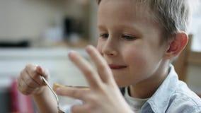 Chłopiec je kawałek chleb z czekoladową pastą po tym jak obiadowy zakończenie w górę zbiory