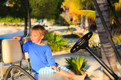 Chłopiec jedzie golfową furę na lato plaży Fotografia Stock