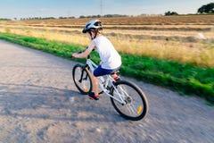 Chłopiec jedzie jego bicykl w białym hełmie obraz royalty free