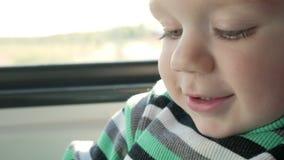 Chłopiec jedzie w poruszającym pociągu blisko okno Ono uśmiecha się i spojrzenia przy książką Zakończenie zbiory wideo