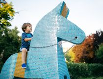 Chłopiec jedzie zabawkarską końską ceramiczną płytkę Zdjęcie Stock