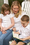 chłopiec jego matka czyta siostry potomstwa Fotografia Royalty Free