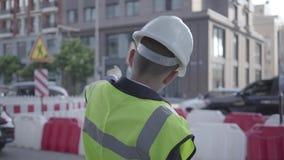 Chłopiec jest ubranym garnituru, zbawczego wyposażenia i konstruktora hełma pozycję na ruchliwie drodze w dużym mieście zbiory wideo