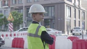 Chłopiec jest ubranym garnituru, zbawczego wyposażenia i konstruktora hełma pozycję na ruchliwie drodze w dużym mieście zbiory