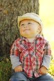 Chłopiec jest ubranym kowbojskiego kapelusz bawić się na naturze Fotografia Stock