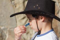 Chłopiec jest ubranym kowbojskiego kapelusz patrzeje niedorzeczną z clothespin Obraz Stock