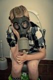 Chłopiec jest ubranym maskę gazową podczas gdy siedzący na toalecie Fotografia Stock