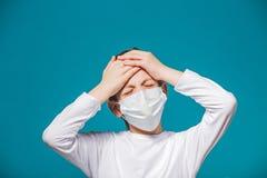 Chłopiec jest ubranym ochrony maskę ma migrenę zdjęcie stock