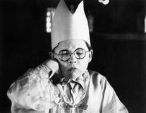 Chłopiec jest ubranym papierowego korony obsiadanie z jego ono przygląda się zamyka (Wszystkie persons przedstawiający no są dług Obraz Royalty Free