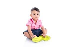 Chłopiec jest ubranym różowego koszulowego obsiadanie nad bielem Zdjęcie Royalty Free