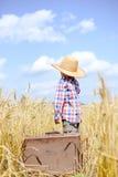 Chłopiec jest ubranym słomianego kapelusz z walizką wewnątrz Obrazy Royalty Free