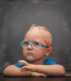 Chłopiec jest ubranym szkła z mądrym spojrzeniem Zdjęcia Royalty Free