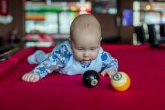 Chłopiec kłaść na czerwonym bilardowym stole obraz stock