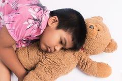 chłopiec kłaść na podłoga z brown misiem zdjęcie royalty free