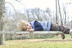 Chłopiec kłaść na wietrzejącej, drewnianej huśtawce, Obraz Stock