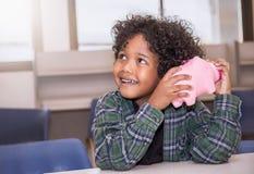 Chłopiec kładzenia pieniądze w prosiątko banka zdjęcie stock