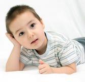 Chłopiec kłama na białym łóżkowym portrecie Zdjęcie Stock