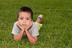 Chłopiec kłama na zielonej trawie, podpiera up twarzy ręki Obrazy Stock