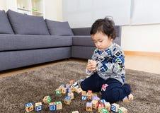 Chłopiec koncentracja na bawić się drewnianego zabawka blok zdjęcie royalty free