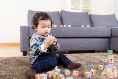 Chłopiec koncentracja na bawić się drewnianego zabawka blok zdjęcie stock