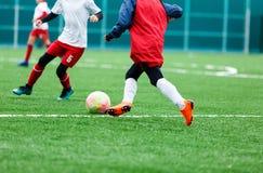 Chłopiec kopie piłki nożnej piłkę Chłopiec biega po piłki na zielonej trawie futbolista w białej i czerwonej koszula chłopiec dry zdjęcie royalty free