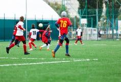 Chłopiec kopie piłki nożnej piłkę Chłopiec biega po piłki na zielonej trawie futbolista w białej i czerwonej koszula chłopiec dry obraz stock