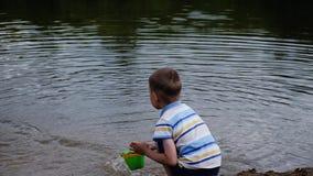 Chłopiec krzyczy wodę i nalewa z wiadra w rzekę z furią Dzieci bawią się w naturze zbiory