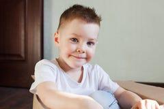 Chłopiec 4 lat blondynka siedzi w pudełku w domu, portret szczęśliwy dziecko, iskrzy emocje, styl życia zdjęcia royalty free