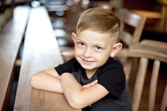 Chłopiec 4-5 lat siedzi przy drewnianym stołem w kawiarni zdjęcia royalty free