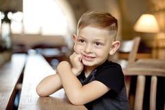 Chłopiec 4-5 lat siedzi przy drewnianym stołem w kawiarni zdjęcie stock