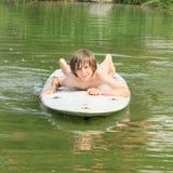 Chłopiec lying on the beach na kipieli Zdjęcie Royalty Free