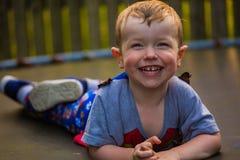 Chłopiec lying on the beach na trampoline śmiać się Zdjęcie Stock